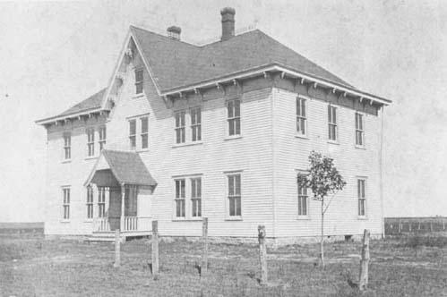 Assumption School on an open prairie